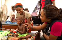 A child eating plumpy nut as health worker and mother look on, Central African Republic.