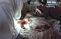 A health worker completes a surgical operation by the light of a mobile phone