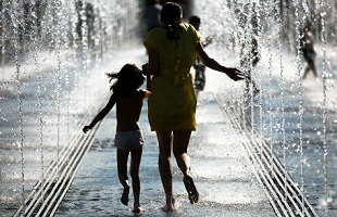 A mother and a child are playing with the fountains, Moscow, Russia.