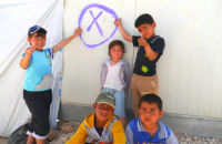 Children point to a circle around the 'x' on the outside of their caravan. The 'x', drawn by a vaccination team, indicates that children were missed during a door-to-door campaign visit. The circle is drawn after a 'mop-up', when all children under five living in the household have been vaccinated.