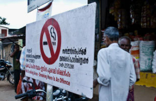 A man walks by a sign designating a no smoking area in India.